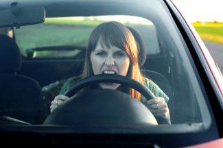 woman biting steering wheel